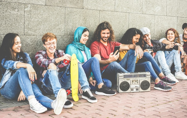 Grupa przyjaciół millenialsów za pomocą smartfonów i słuchania muzyki na świeżym powietrzu
