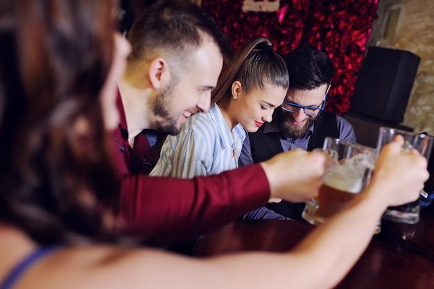 Grupa przyjaciół - młodzi chłopcy i dziewczęta piją piwo, rozmawiają i uśmiechają się do baru