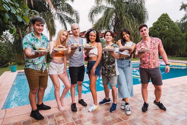 Grupa przyjaciół na imprezie poool z hamburgerami