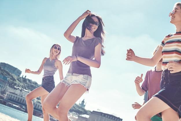 Grupa przyjaciół na plaży szczęśliwych młodych przyjaciół bawi się i świętuje podczas skakania i