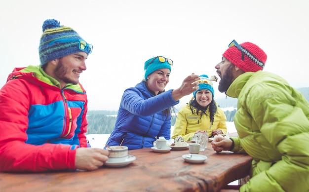 Grupa przyjaciół na zewnątrz picia gorących napojów