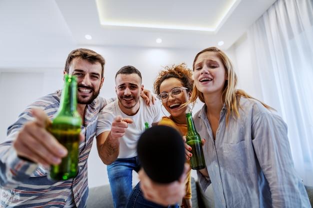Grupa przyjaciół o imprezie karaoke w domu. wszyscy wskazują na aparat.