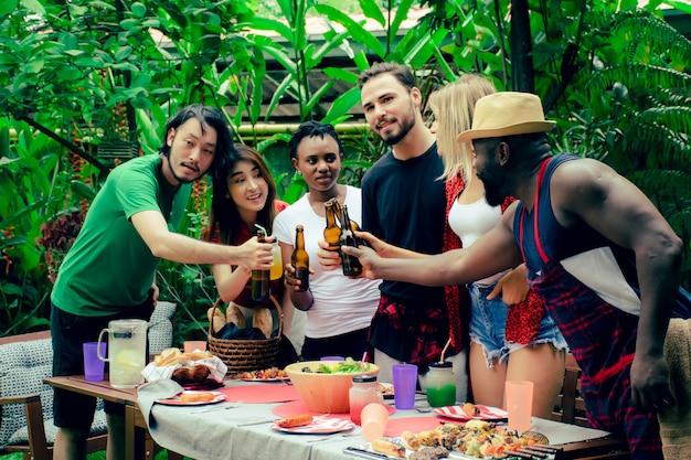 Grupa przyjaciół o imprezie z grilla w przyrodzie.