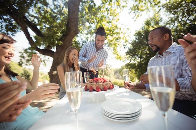 Grupa przyjaciół obchodzi urodziny womans w restauracji na świeżym powietrzu
