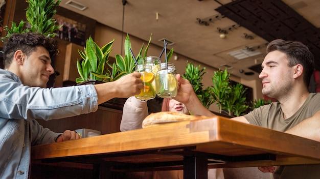 Grupa przyjaciół odpoczywająca w pubie. jedzenie, picie, jedzenie na stole. przyjaźń