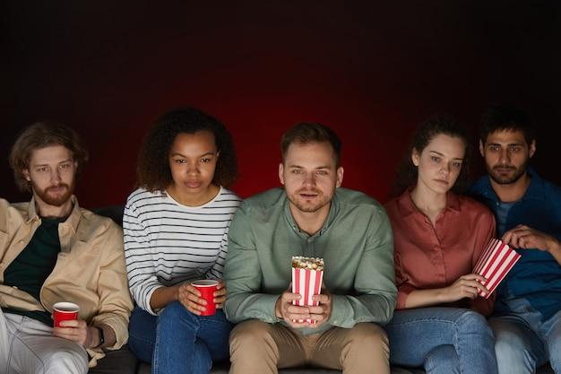 Grupa przyjaciół ogląda filmy w domu jedząc przekąski i popcorn, siedząc na dużej kanapie w ciemnym pokoju
