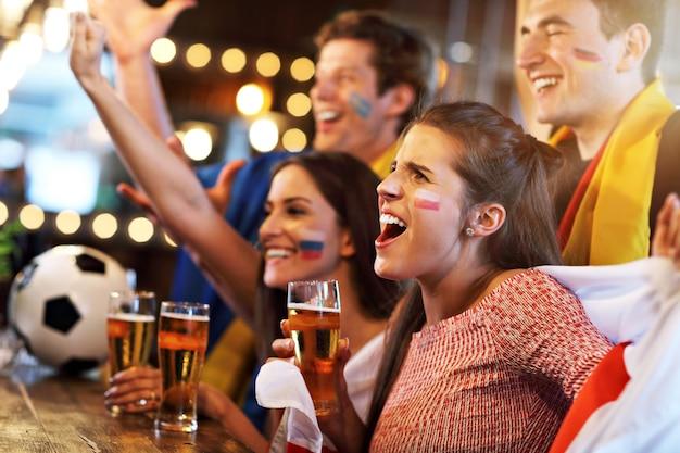 Grupa przyjaciół ogląda mecz piłki nożnej w pubie