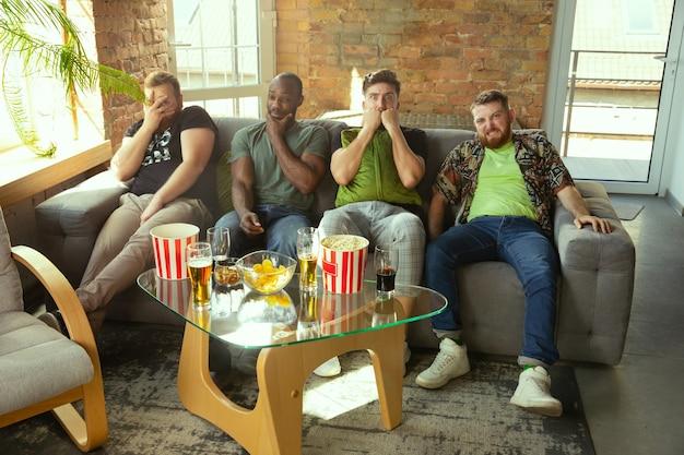 Grupa przyjaciół ogląda mecz w telewizji w domu. fani sportu spędzający czas i dobrze się bawiąc