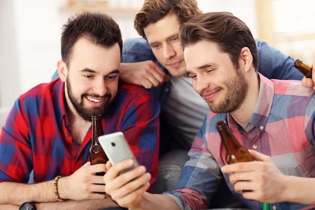 Grupa przyjaciół oglądająca smartfona siedząca na kanapie w salonie w domu