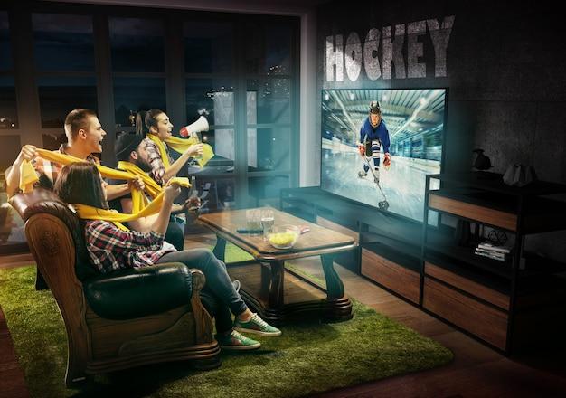 Grupa przyjaciół oglądająca telewizję, mecz hokejowy, mistrzostwa, gry sportowe. emocjonalni mężczyźni i kobiety dopingują ulubioną drużynę hokejową nastolatków. pojęcie przyjaźni, sportu, rywalizacji, emocji.