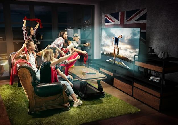 Grupa przyjaciół oglądająca telewizję, mecz, mistrzostwa, gry sportowe. emocjonalni mężczyźni i kobiety dopingują flagą ulubionego biegacza wielkiej brytanii. pojęcie przyjaźni, sportu, rywalizacji, emocji.