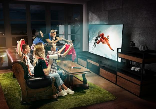 Grupa przyjaciół oglądająca telewizję, mecz, mistrzostwa, gry sportowe. emocjonalni mężczyźni i kobiety dopingują ulubionego snowboardzistę, patrzą na walkę o piłkę. pojęcie przyjaźni, rywalizacji, emocji.