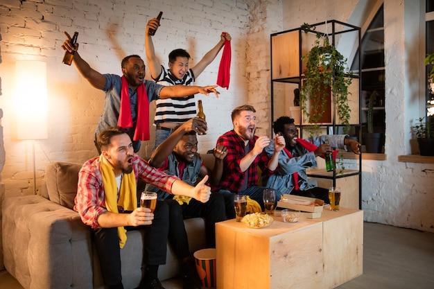 Grupa przyjaciół oglądających mecz w telewizji razem emocjonalnych fanów kibicujących ulubionej drużynie oglądającej ekscytującą grę koncepcji przyjaźni, spędzania wolnego czasu, emocji