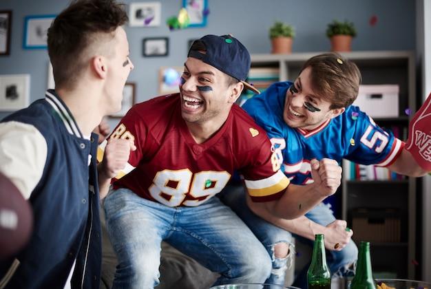Grupa przyjaciół oglądających piłkę nożną w domu