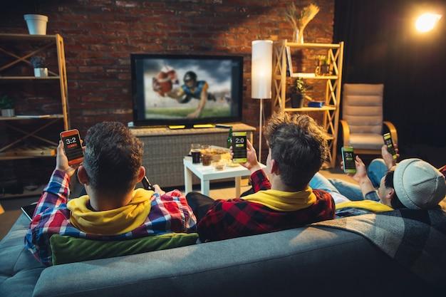 Grupa przyjaciół oglądanie telewizji, mecz sportowy razem. emocjonalni kibice dopingują ulubioną drużynę, oglądają emocjonującą piłkę nożną. pojęcie przyjaźni, spędzania wolnego czasu, emocji.
