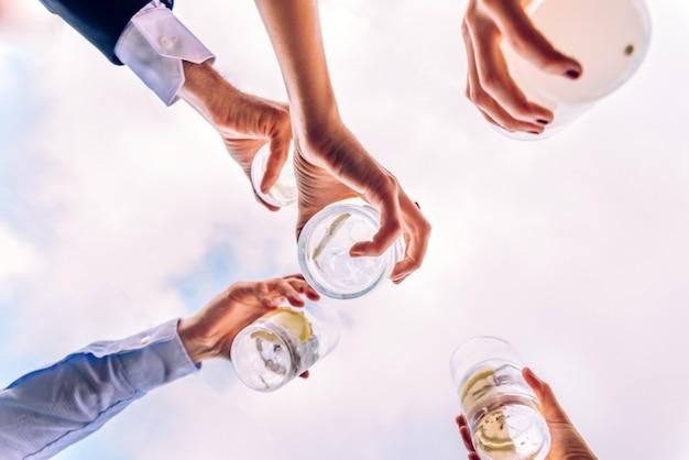 Grupa przyjaciół opiekania z kilkoma szklankami alkoholu z niebem w tle