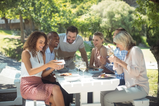 Grupa przyjaciół patrząc obraz w telefonie komórkowym