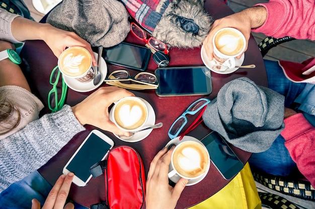 Grupa przyjaciół picia cappuccino w restauracjach kawiarni