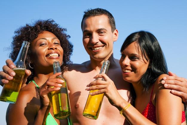 Grupa przyjaciół picia piwa w stroje kąpielowe
