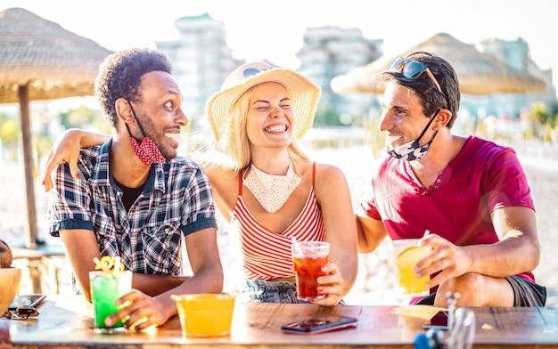 Grupa przyjaciół picie koktajli w chiringuito bar na plaży z otwartymi maskami na twarz