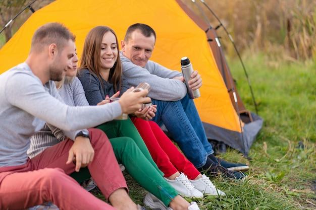 Grupa przyjaciół pije rozgrzewający napój z termosu w chłodny wieczór przy kominku w lesie. zabawa na kempingu z przyjaciółmi