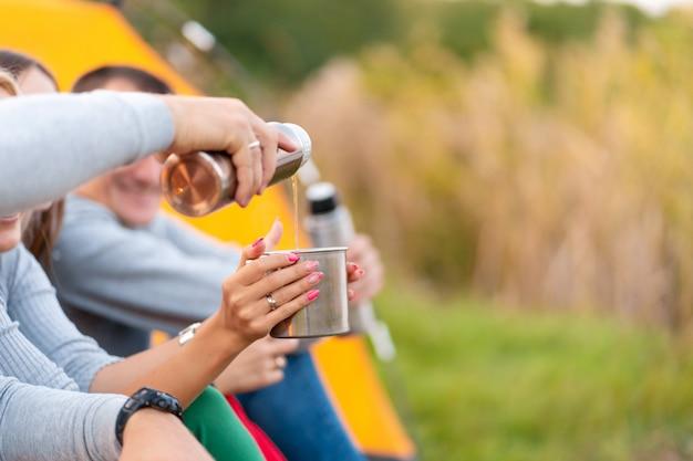 Grupa przyjaciół pije rozgrzewający napój z termosu w chłodny wieczór przy kominku w lesie