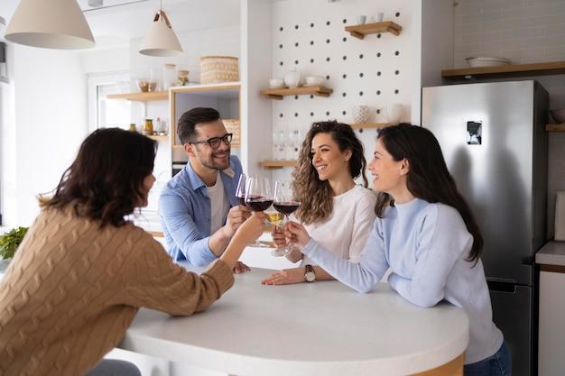 Grupa przyjaciół pije wino w kuchni