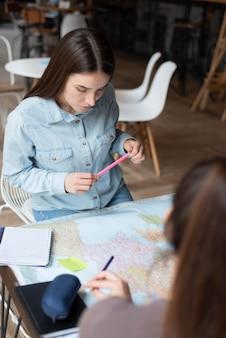 Grupa przyjaciół planująca podróż w kawiarni