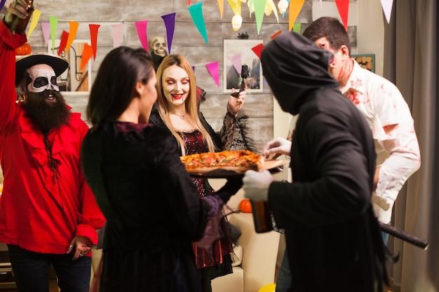 Grupa przyjaciół podekscytowana pyszną pizzą na imprezie halloween.