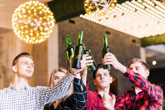 Grupa przyjaciół, podnosząc butelki piwa w pubowej restauracji