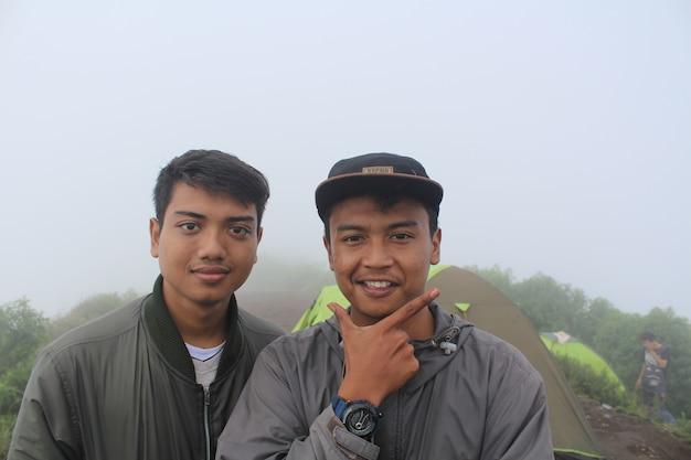 Grupa przyjaciół podróżników wędrujących po zielonych wzgórzach z pięknymi przyjaciółmi wspinającymi się na górę