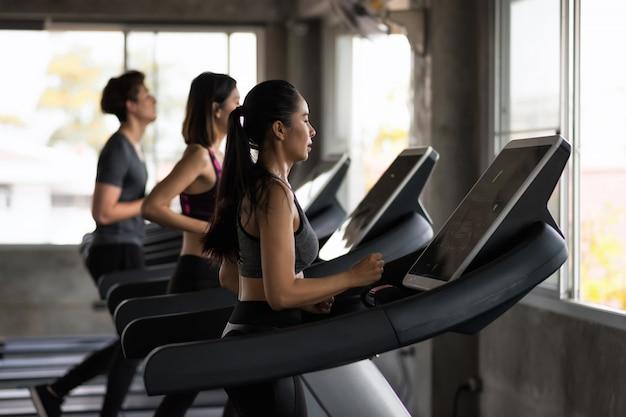 Grupa przyjaciół prowadzi bieżnie w siłowni