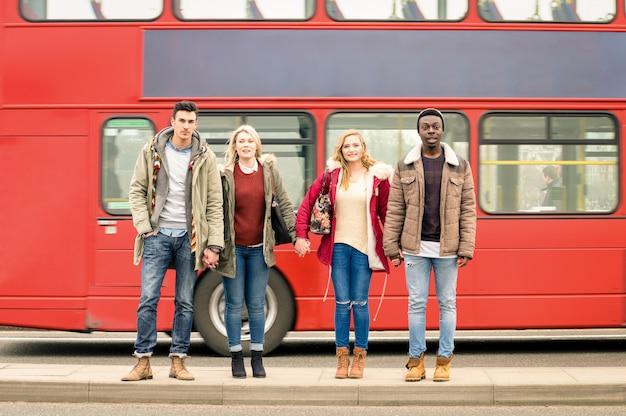 Grupa przyjaciół przez jezdnię z tradycyjnym czerwonym autobusem za