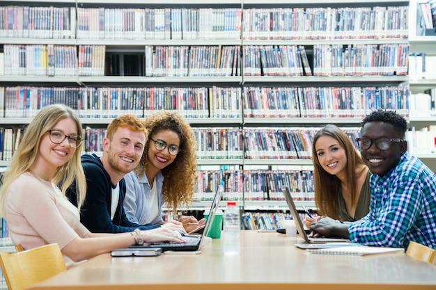 Grupa przyjaciół przyglądając się aparatu w bibliotece uniwersyteckiej.