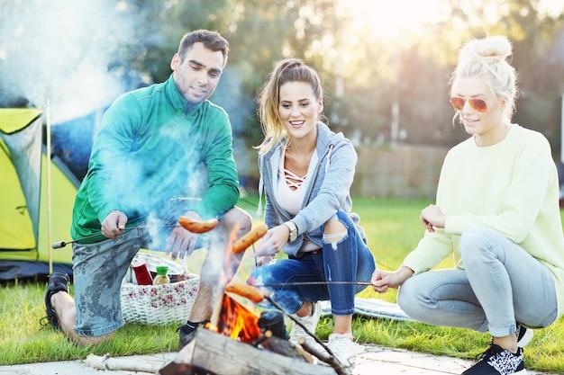Grupa przyjaciół przygotowująca kiełbaski na ognisku