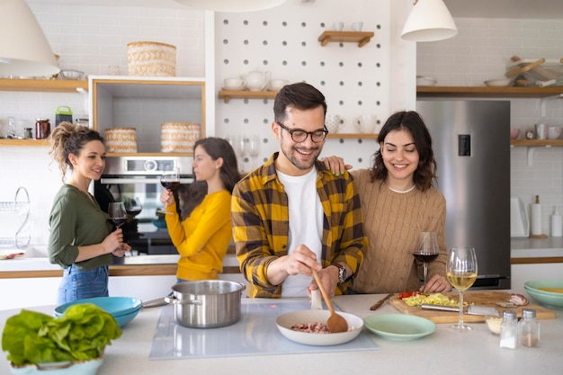 Grupa przyjaciół przygotowuje posiłek w kuchni