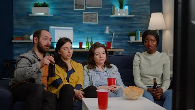 Grupa przyjaciół rasy mieszanej relaksuje się na kanapie podczas oglądania filmu rozrywkowego w telewizji, śmiejąc się...