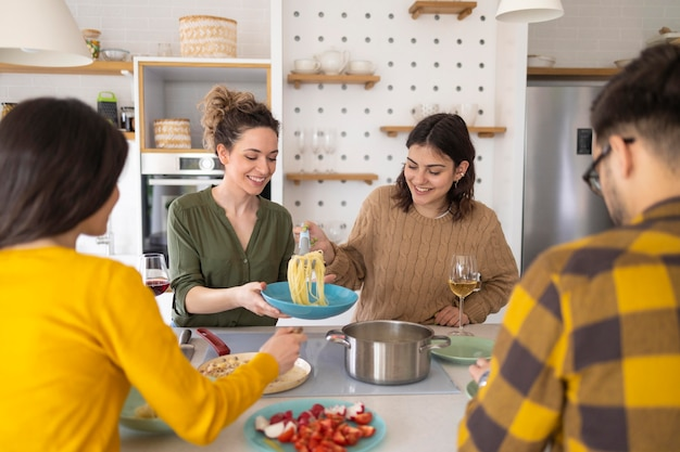 Grupa przyjaciół razem jeść makaron w kuchni