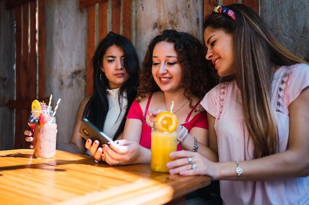 Grupa przyjaciół razem pije sok owocowy i patrzy na smartfona.
