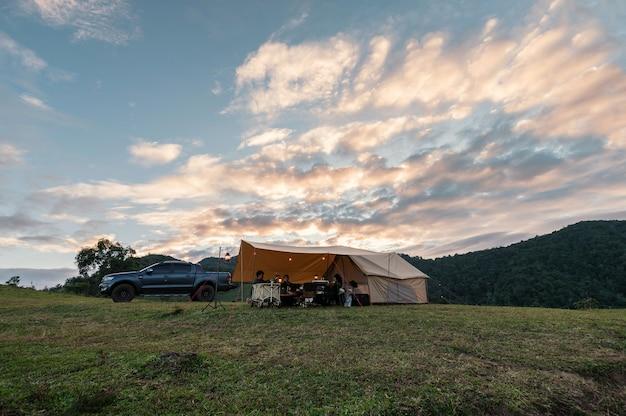 Grupa przyjaciół relaks w dużym namiocie i pickup zaparkowany na wzgórzu w okolicy na wakacje na kempingu