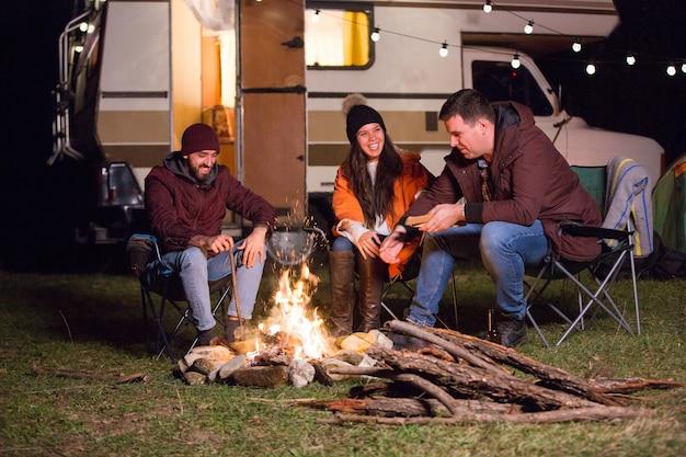 Grupa przyjaciół relaksująca i śmiejąca się razem wokół ogniska w górach. retro samochód kempingowy.