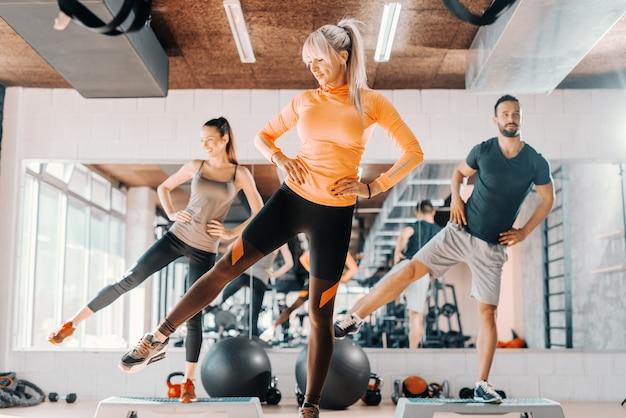 Grupa przyjaciół robi ćwiczenia fitness na nogi w siłowni. w tle ich odbicie lustrzane.