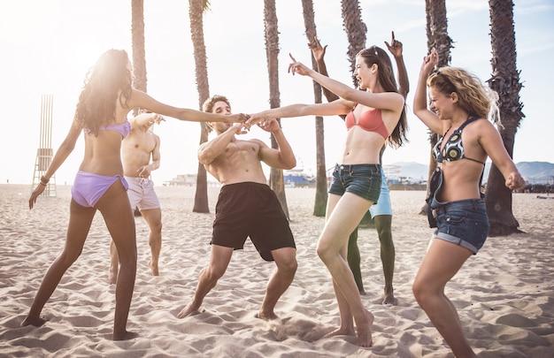 Grupa przyjaciół robi wielkie imprezy i gry na plaży