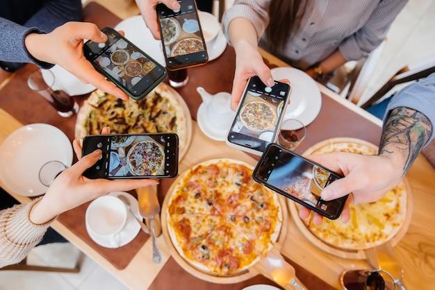 Grupa przyjaciół robi zbliżenie pysznej pizzy na blog, pizzerię