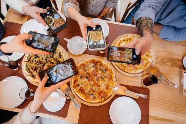 Grupa przyjaciół robi zbliżenie pysznej pizzy na blog, pizzerię.