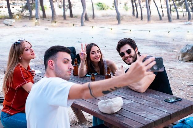 Grupa przyjaciół robi zdjęcia smartfonem na terenie piknikowym