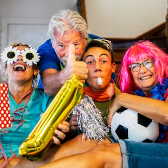 Grupa przyjaciół rodziny kibiców piłki nożnej z radością oglądając mecz w telewizji - kaukaski w wieku mieszanym, młodzi dorośli i dojrzali ludzie bawią się razem patrząc sport w domu