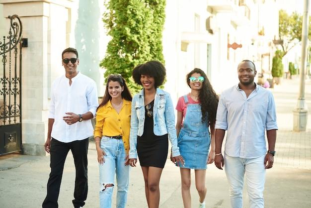 Grupa przyjaciół różnych narodowości spaceruje po mieście