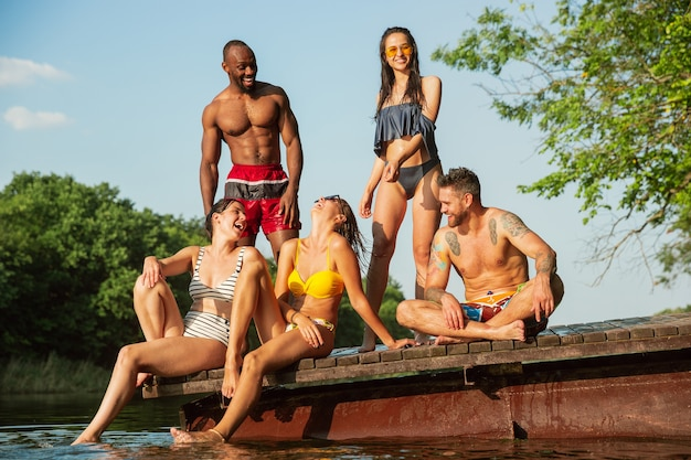 Grupa przyjaciół rozpryskiwania wody i śmiejąc się na molo na rzece