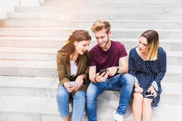 Grupa przyjaciół siedząc na schody patrząc na ekran telefonu komórkowego